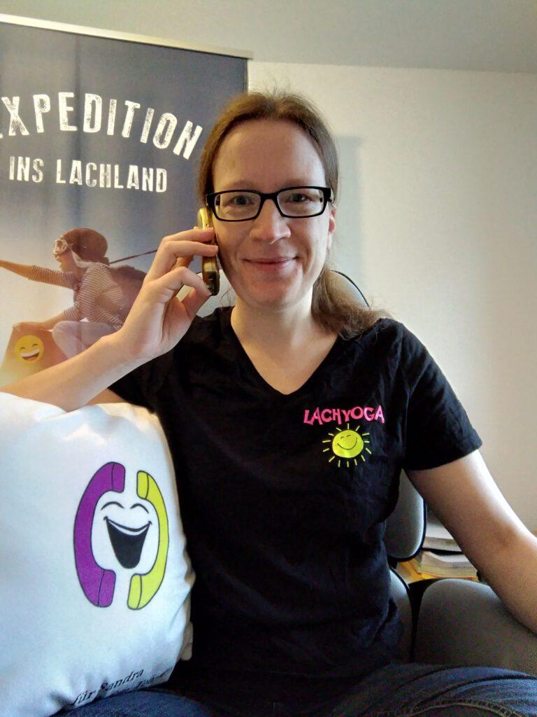 """Sandra mit Lachtelefon-Kissen und goldenem Telefon vor einem Roll-Up """"Expedition ins Lachland"""""""